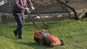 Ενήλικο άτομο με τον ηλεκτρικό χορτοκόπτη, κοπή χορτοταπήτων Κηπουρός που τακτοποιεί έναν κήπο φιλμ μικρού μήκους