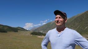 Ενήλικο άτομο πορτρέτου που στέκεται στο τοπίο βουνών και που απολαμβάνει το καθαρό αέρα φιλμ μικρού μήκους
