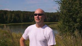 Ενήλικο άτομο πορτρέτου στα γυαλιά ηλίου στο πράσινα δάσος υποβάθρου και το νερό λιμνών φιλμ μικρού μήκους