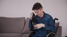 Ενήλικο άτομο στην αναπηρική καρέκλα που κρατά το κράνος εικονικής πραγματικότητας στα χέρια φιλμ μικρού μήκους