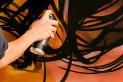 Ενήλικο αρσενικό χρώμα καλλιτεχνών γκράφιτι που ψεκάζει τον τοίχο, Στοκ Εικόνες