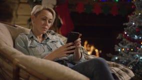 Ενήλικο γυναικών στο smartphone στη νύχτα Χριστουγέννων από το διακοσμημένο δέντρο φιλμ μικρού μήκους
