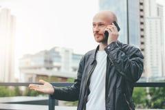 Ενήλικο ελκυστικό φαλακρό γενειοφόρο άτομο που μιλά από κινητό στην οδό πόλεων στοκ φωτογραφίες με δικαίωμα ελεύθερης χρήσης