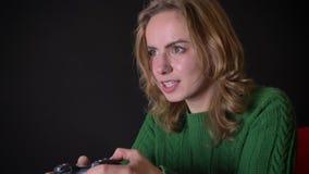 Ενήλικο καυκάσιο θηλυκό πορτρέτου ο κινηματογραφήσεων σε πρώτο πλάνο που παίζει τα τηλεοπτικά παιχνίδια με την απόλαυση στο εσωτε φιλμ μικρού μήκους