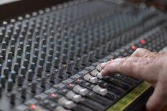 Ενήλικο χέρι ατόμων που ελέγχει τους ολισθαίνοντες ρυθμιστές ενός αναμίκτη σε ένα στούντιο στοκ φωτογραφία με δικαίωμα ελεύθερης χρήσης