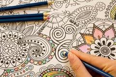 Ενήλικα βιβλία χρωματισμού με τα μολύβια, νέα ανακουφίζοντας τάση πίεσης, χρωματισμός προσώπων έννοιας mindfulness επεξηγηματικός Στοκ Φωτογραφίες