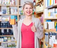 Ενήλικες θηλυκές σειρές ξεφυλλίσματος πελατών των προϊόντων φροντίδας δέρματος Στοκ φωτογραφία με δικαίωμα ελεύθερης χρήσης