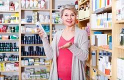 Ενήλικες σειρές ξεφυλλίσματος πελατών γυναικών των προϊόντων φροντίδας δέρματος Στοκ εικόνα με δικαίωμα ελεύθερης χρήσης