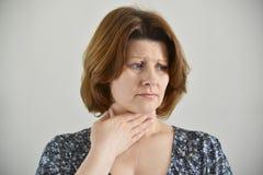 Ενήλικη γυναίκα με έναν επώδυνο λαιμό στο ελαφρύ υπόβαθρο στοκ εικόνα
