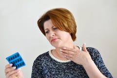 Ενήλικη γυναίκα με έναν επώδυνο λαιμό στοκ εικόνα