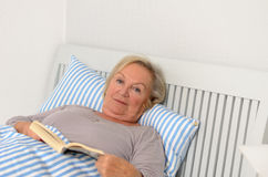 Ενήλικη γυναίκα με το βιβλίο που βρίσκεται στο κρεβάτι Στοκ φωτογραφία με δικαίωμα ελεύθερης χρήσης