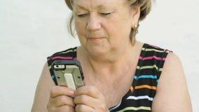 Ενήλικη γυναίκα που κρατά ένα έξυπνο τηλέφωνο υπαίθρια απόθεμα βίντεο