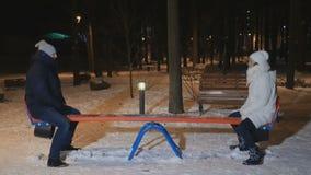 Ενήλικη ταλάντευση ανδρών και γυναικών seesaw στο χειμερινό πάρκο βραδιού απόθεμα βίντεο