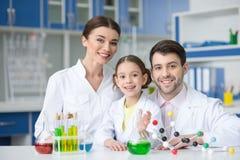 Ενήλικοι επιστήμονες και σπουδαστής μικρών κοριτσιών που εργάζονται μαζί στο χημικό εργαστήριο και που χαμογελούν στη κάμερα στοκ εικόνες με δικαίωμα ελεύθερης χρήσης