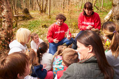 Ενήλικοι και παιδιά που εξετάζουν τη φωλιά του πουλιού στο κέντρο δραστηριότητας στοκ εικόνα