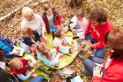 Ενήλικοι και παιδιά που εξετάζουν τη φωλιά του πουλιού στο κέντρο δραστηριότητας στοκ φωτογραφία