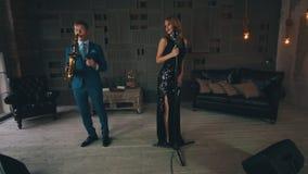 Ενήλικος αοιδός τζαζ στο καμμένος φόρεμα που αποδίδει στη σκηνή με το χορό saxophonist φιλμ μικρού μήκους