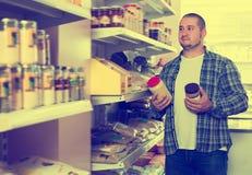 Ενήλικος αρσενικός πελάτης που επιλέγει τα ζυμαρικά των καρυδιών Στοκ Εικόνες