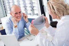 Ενήλικος γιατρός και αρσενικός πελάτης που επιλέγουν τα γυαλιά Στοκ εικόνα με δικαίωμα ελεύθερης χρήσης