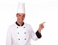 Ενήλικος επαγγελματικός αρχιμάγειρας που δείχνει το αριστερό του Στοκ Εικόνες