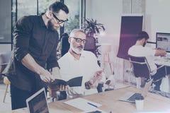 Ενήλικος επιχειρηματίας και ο βοηθός του που κάνουν το μεγάλο 'brainstorming' στο σύγχρονο γραφείο Γενειοφόρο άτομο που μιλά με τ Στοκ Εικόνες