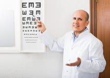 Ενήλικος οπτικός που παρουσιάζει σύμβολα του διαγράμματος Snellen στοκ εικόνες