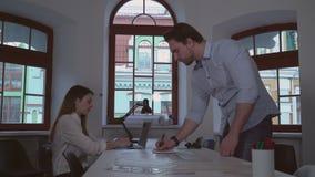 Ενήλικος σχεδιαστής και βοηθητική συνεδρίαση στο γραφείο απόθεμα βίντεο