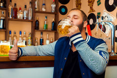 Ενήλικος τύπος σε έναν φραγμό που πίνει ένα εύγευστο ποτήρι της ελαφριάς μπύρας Στοκ Εικόνες