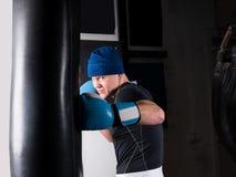Ενήλικος φίλαθλος μπόξερ στα εγκιβωτίζοντας γάντια που εκπαιδεύει με τον εγκιβωτισμό punchin Στοκ Εικόνες