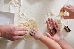 Ενήλικος χεριών, μπισκότα μαγείρων παιδιών στην κινηματογράφηση σε πρώτο πλάνο κουζινών Στοκ Εικόνα