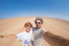 Ενήλικο ζεύγος που παίρνει selfie στο δρόμο αμμοχάλικου στην έρημο Namib, εθνικό πάρκο Namib Naukluft, κύριος προορισμός ταξιδιού στοκ εικόνες