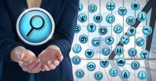 Ενίσχυση - εικονίδιο αναζήτησης γυαλιού με τα διάφορα apps και επιχειρηματίας με την παλάμη χεριών ανοικτή στο γραφείο πόλεων Στοκ Εικόνα
