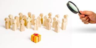 Ενίσχυση - το γυαλί εξετάζει τη μεγάλη ομάδα ανθρώπων που εξετάζει ένα δώρο Η έννοια της επιλογής ενός καλού δώρου, ένας περιορισ στοκ φωτογραφία με δικαίωμα ελεύθερης χρήσης