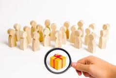 Ενίσχυση - το γυαλί εξετάζει τη μεγάλη ομάδα ανθρώπων που εξετάζει ένα δώρο επιλέγοντας ένα καλό δώρο, ένας περιορισμένος αριθμός στοκ εικόνα