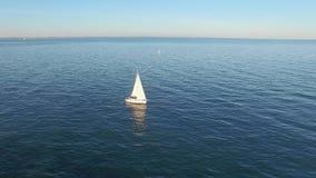 Εναέρια άποψη από το copter του γιοτ πανιών που πλέει εν πλω Μπλε θάλασσα με τις αντανακλάσεις στο νερό απόθεμα βίντεο
