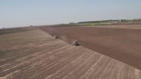 Εναέρια άποψη δύο τρακτέρ που ακολουθούν την αντίθετη κατεύθυνση και που καλλιεργούν το έδαφος Οργώνοντας τομέας γεωργικών τρακτέ απόθεμα βίντεο