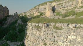 Εναέρια άποψη ενός κοριτσιού σε μια ηλιόλουστη συνεδρίαση στην άκρη ενός βράχου σε ένα φαράγγι βουνών μια ηλιόλουστη ημέρα Αντίστ φιλμ μικρού μήκους