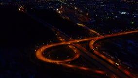 Εναέρια άποψη ενός μεγάλου φωτισμένου συνόλου οδικών συνδέσεων τη νύχτα των αυτοκινήτων και των φορτηγών φιλμ μικρού μήκους