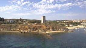 Εναέρια άποψη ενός μεσαιωνικού πύργου στην παραλία Nea Fokea και μιας μικρής βάρκας στο λιμάνι, Halkidiki Ελλάδα, οπίσθια μετακίν φιλμ μικρού μήκους