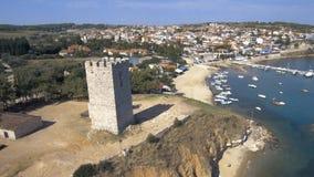 Εναέρια άποψη ενός μεσαιωνικού πύργου στην παραλία Nea Fokea και μιας μικρής βάρκας στο λιμάνι, το Halkidiki Ελλάδα, την κίνηση π απόθεμα βίντεο