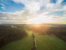 Εναέρια άποψη ενός όμορφου ηλιοβασιλέματος πέρα από το αγροτικό τοπίο με τα δάση και τους πράσινους τομείς Στοκ Εικόνες