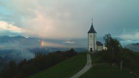 Εναέρια άποψη κηφήνων της εκκλησίας Αγίου Tomas στον ανώτερο της κοιλάδας Sava στη Σλοβενία Τοπίο βουνών με το ουράνιο τόξο φιλμ μικρού μήκους