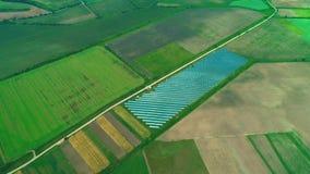 Εναέρια άποψη κηφήνων του μεγάλου ηλιακού αγροκτήματος στους πράσινους τομείς Ζουμ 4K φιλμ μικρού μήκους