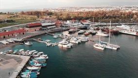 Εναέρια άποψη κηφήνων του όμορφου λιμανιού πόλεων με τα γιοτ και τα αλιευτικά σκάφη και του για τους πεζούς περιπάτου τουριστών σ φιλμ μικρού μήκους