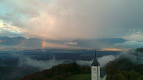 Εναέρια άποψη κηφήνων Jamnik, Σλοβενία Ουράνιο τόξο, Άλπεις και εκκλησία του ST Primoz απόθεμα βίντεο