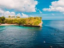 Εναέρια άποψη με τα surfers στον τροπικό μπλε ωκεανό και το ακρωτήριο στο Μπαλί στοκ εικόνα