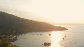 Εναέρια άποψη με το βουνό, τη θάλασσα και τις βάρκες στο Μπαλί στο ηλιοβασίλεμα απόθεμα βίντεο