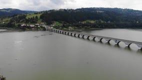 Εναέρια άποψη μιας γέφυρας πέρα από έναν ποταμό στην κοιλάδα βουνών απόθεμα βίντεο