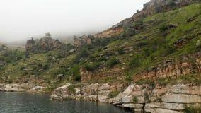 Εναέρια άποψη μιας δύσκολης τυρκουάζ λίμνης βουνών ακτών μεταξύ των λόφων στο νεφελώδη καιρό και την ομίχλη Τοπία του Βορρά φιλμ μικρού μήκους