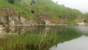 Εναέρια άποψη μιας δύσκολης τυρκουάζ λίμνης βουνών ακτών μεταξύ των λόφων στο νεφελώδη καιρό και την ομίχλη Τοπία του Βορρά απόθεμα βίντεο